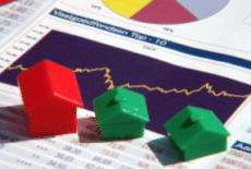 Housing report with monopoly house pieces sitting on top