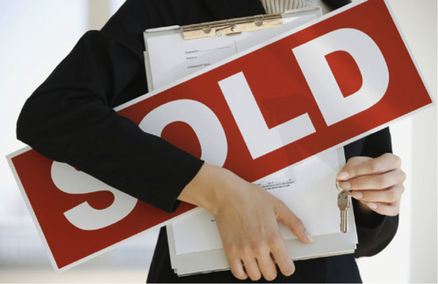 Agent holding sold sign and house keys